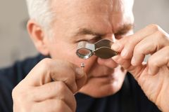 Male jeweler evaluating earring in workshop. Closeup royalty free stock photo