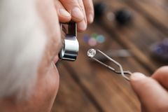 Male jeweler evaluating precious gemstone in workshop. Closeup royalty free stock photo