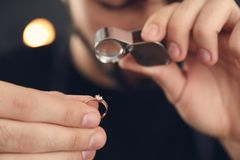 Male jeweler evaluating ring in workshop. Closeup stock images