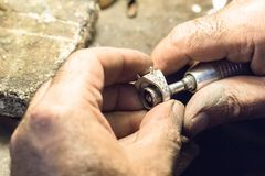 Jeweler polishing a ring using a sandpaper on a slotted mandrel. Royalty Free Stock Image