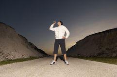 Male Jogger Drinking Water On Country Street stock image