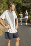 Male Jogger With Female Friends In Background. Male jogger pausing for breath on path with female friends in background Royalty Free Stock Images
