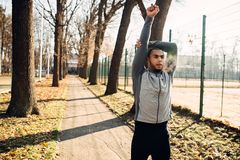 Male jogger on fitness workout in autumn park. Runner in sportswear on training outdoor. Sportsman warming up before run royalty free stock images