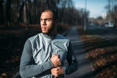 Male jogger in motion on workout outdoors. Runner in sportswear on training in park. Jogging or running stock photography