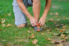 Male jogger tying laces on his shoes outside.  Stock Images