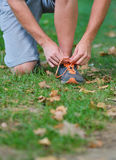 Male jogger tying laces on his shoes outside.  Stock Photography