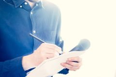 Male journalist at news conference, holding microphone and taking notes. Cut-out of a male journalist in a blue shirt at a news conference who is taking notes stock photography