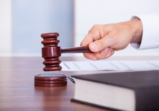 Male judge in a courtroom. Striking The Gavel Royalty Free Stock Photo
