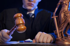 Male judge in a courtroom striking the gavel Stock Photo