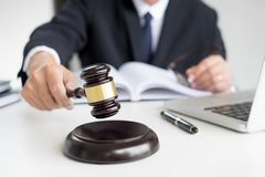 Male Judge lawyer In A Courtroom Striking The Gavel on sounding. Block Royalty Free Stock Photos