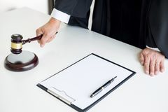 Male Judge lawyer In A Courtroom Striking The Gavel on sounding Stock Photography
