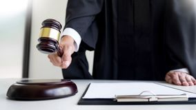 Male Judge lawyer In A Courtroom Striking The Gavel on sounding. Block Royalty Free Stock Images