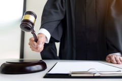 Male Judge lawyer In A Courtroom Striking The Gavel on sounding. Block Stock Photography