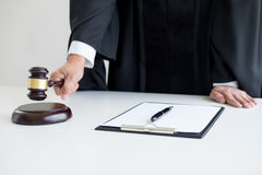 Male Judge lawyer In A Courtroom Striking The Gavel on sounding. Block Stock Photo