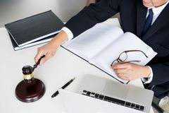 Male Judge lawyer In A Courtroom Striking The Gavel on sounding. Block Stock Image