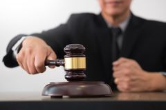 Male Judge lawyer In A Courtroom Striking The Gavel on sounding Stock Photo