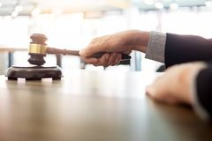 Male Judge lawyer In A Courtroom Striking The Gavel on sounding Royalty Free Stock Photography
