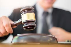 Male Judge lawyer In A Courtroom Striking The Gavel on sounding Royalty Free Stock Image
