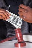 Male Judge Putting Dollar In His Pocket stock images