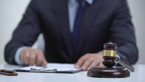 Male judge signing document banging gavel on block, court determines sentence. Stock footage stock footage