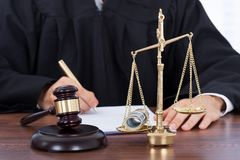 Male judge signing document in courtroom Stock Photos