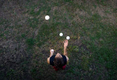 Male juggler juggling with balls from above. Male juggler juggling with four white balls, shot from above stock photos