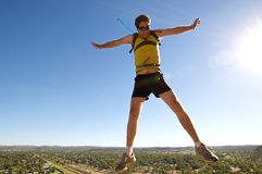 Male jumping infront of Vista. Male star jumping on top of cliff Stock Image