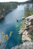 Male jumping off cliff into horseshoe lake Stock Photos
