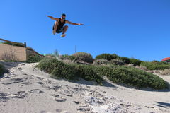 Male jumping off the sand dunes at Cottesloe Beach Royalty Free Stock Image
