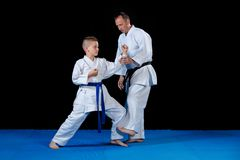 Male karate instructor training little children in dojo.  Stock Images