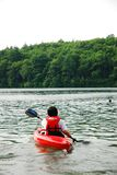 Kayaker heading out. A male kayaker paddles into Walden Pond near Concord, Massachusetts stock photo