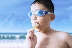 Male kid bites ice cream at seaside Royalty Free Stock Images