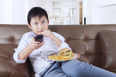 Male kid enjoy fast food at home Stock Photography
