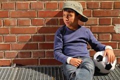 Male kid with a football. Male kid sitting outside with a football royalty free stock photography