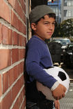Male kid with a football. Male kid standing outside with a football royalty free stock image