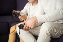 Hands holding joysticks, father and son playing video games, clo Stock Photos