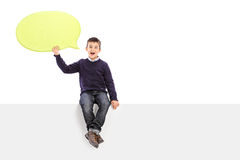 Male kid holding a speech bubble seated on panel Royalty Free Stock Images