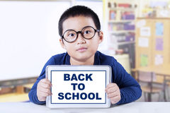 Male kid holds tablet and back to school Royalty Free Stock Images