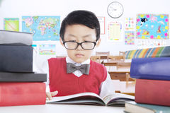 Male kid reading books lesson in classroom. Cute little boy studying in the classroom and reading lesson books while wearing glasses, shot in the school Stock Image