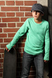 Male kid with a skateboard. Male kid standing outside with a skateboard stock photo