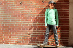 Male kid with a skateboard. Male kid standing outside on a skateboard stock photos