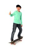 Male kid with a skateboard. Male kid standing on a skateboard with thump high stock image