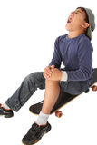 Male kid with a skateboard. Male kid sitting on a skateboard and crying royalty free stock photo