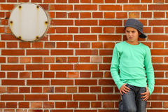 Male kid standing on a Brick stone wall. Male kid standing outside on a Brick stone wall and waiting stock image