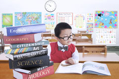 Male kid studying with lesson books in class Stock Image