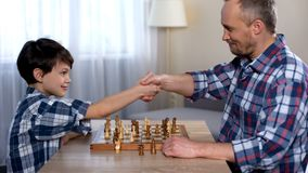 Male kid winning chess with his father, little son shaking hand with dad, hobby stock photo