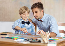 Male kindergarten teacher. Drawing picture with child Stock Photos