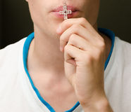 Male kissing a cross Royalty Free Stock Image