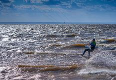 A male kiteboarder rides on a board on a large river. He performs various exercises while moving on water. stock image