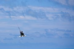 Male Kitesurfer grabing his board Royalty Free Stock Photos